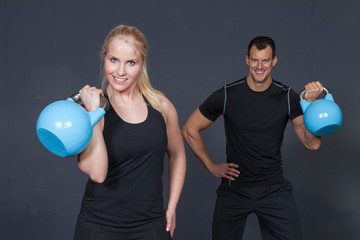 man and woman lifting kettle bell
