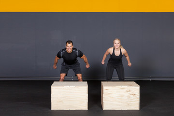 Man and woman jumping on a box - cross fit