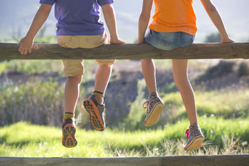 Children sitting on fence with feet dangling