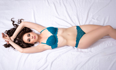 Top view of curly brunette in blue lingerie