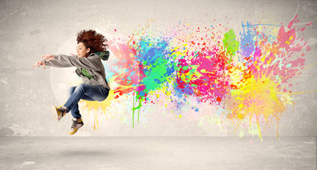 Happy teenager jumping with colorful ink splatter on urban backg