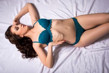 Seductive underwear model posing curved at camera