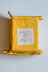 Yellow parcel from China on white.