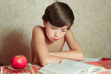 handsome preteen boy reading book with apple