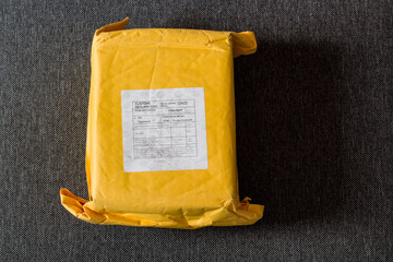 Yellow parcel from China on gray textile.
