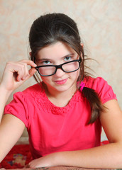 beautiful preteen girl in correction glasses
