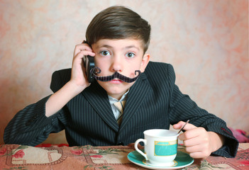 school boy in businessman suit  cup of caffee and mustache