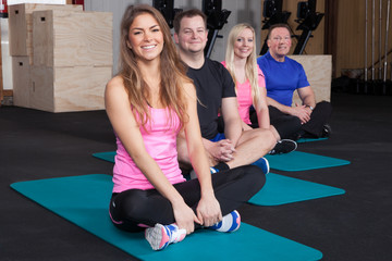 Sports group people preparing for sport exercise sitting on yog