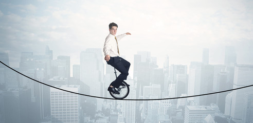 Brave guy riding a monocycle on a rope above cityscape