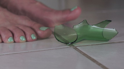 Female Feet With Broken Glass on Floor Side View