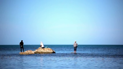 Fishermans at the sea standing on stones go fishing. Video