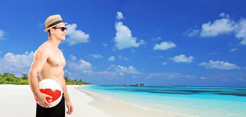 Man holding a beach ball by the sea