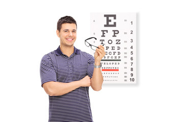Young guy holding glasses in front of an eye chart