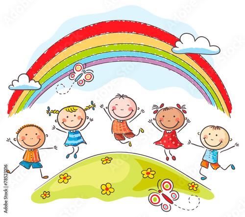 Fototapeta Kids jumping with joy underneath a rainbow