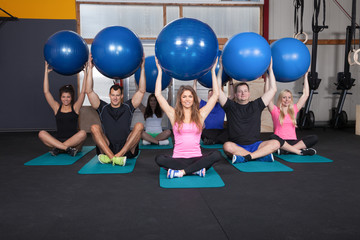 Medicine ball fitness training - sports team sitting on yoga mat