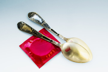 Two golden teaspoons with red hearts and a red condom