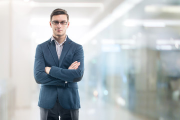 Young handsome businessman wearing glasses in the office and