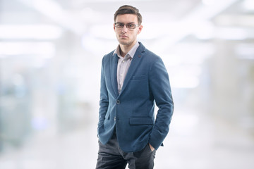 Young handsome guy wearing glasses in the office and standing