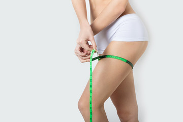athletic girl measures thighs and legs with tape, fitness