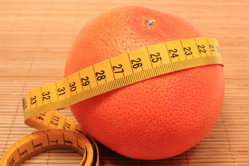 Fresh grapefruit and tape measure on wooden background