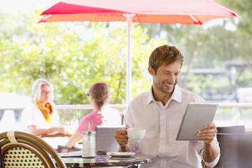 Man drinking coffee looking at digital tablet in outdoor cafŽ