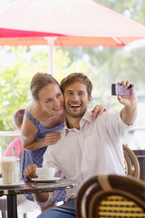 Couple taking selfie in outdoor cafe