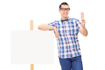 Joyful man holding an ice cream next to a banner