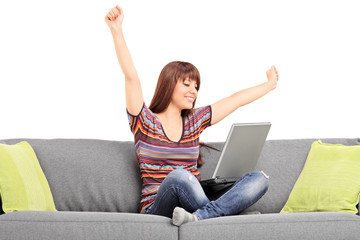 Joyful woman working on laptop seated on sofa