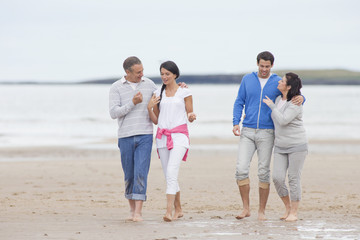 Parents and adult offspring walking together on beach