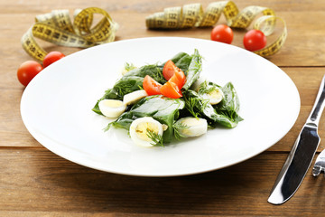 Salad with quail egg and basil in plate