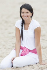 Smiling woman sitting in sand on beach