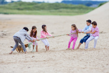 Children playing tug-of-war on beach