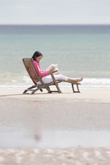Woman reading book in deck chair on beach