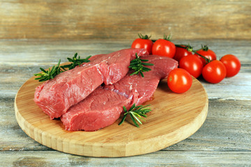 Raw beef steak with rosemary and cherry tomatoes