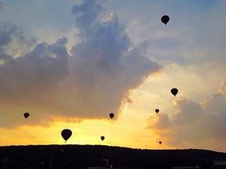 multiple hot air balloons sunset