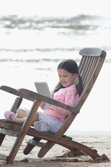 Girl using digital tablet in deck chair on beach