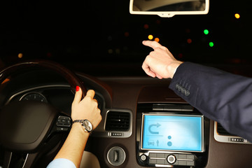 Woman and man in modern car at night in city, close-up