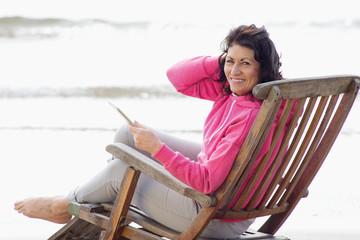 Older woman using digital tablet in deck chair on beach