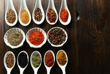 Different kinds of spices in bowls and spoons, close-up,