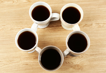 Cups of coffee on wooden table background