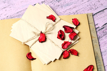Love letters and rose petals on wooden background