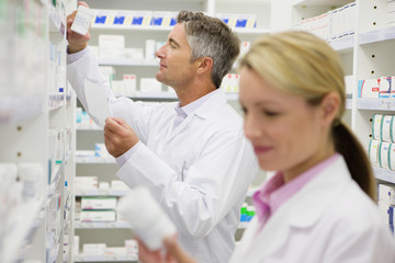 Pharmacist searching for bottle of medication on pharmacy shelves