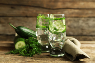 Glasses with fresh organic cucumber water on wooden table