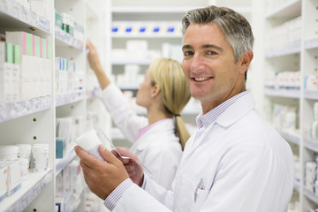 Pharmacists holding bottle of prescription medication in pharmacy