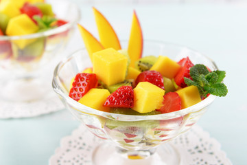 Fruit salad with mint in glassware