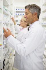 Pharmacists searching for medication on pharmacy shelves