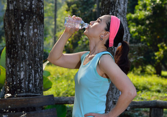 Middle aged woman drinking water after exercising