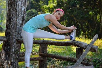 Middle aged woman stretching in the park