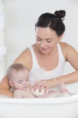 Smiling mother bathing happy baby in bathtub