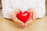 Frau hält rotes Herz in der Hand